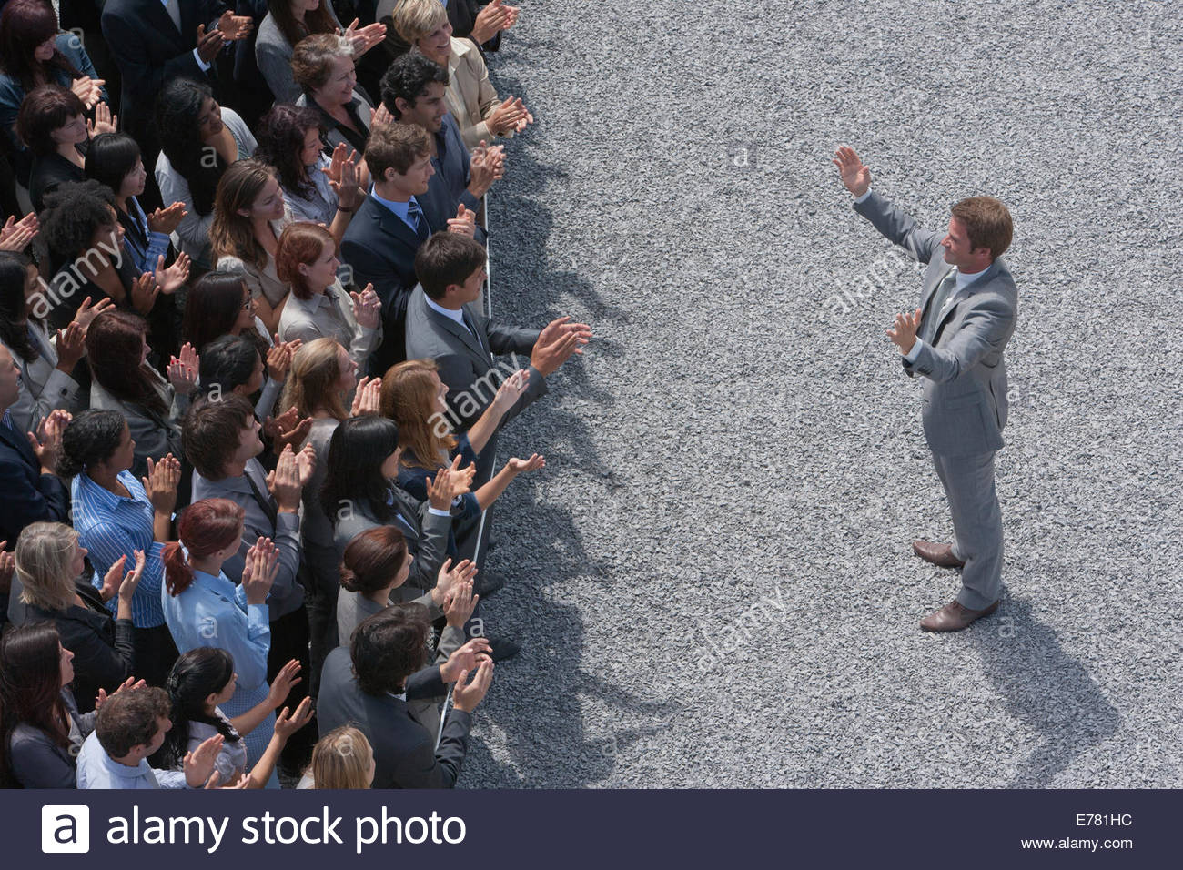 Businessman addressing clapping crowd - Stock Image