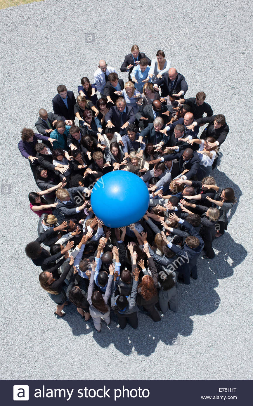 Crowd of business people in huddle reaching for globe - Stock Image