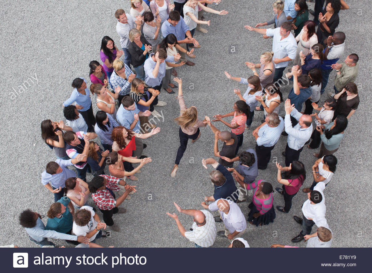 Woman walking between two groups of people, people clapping - Stock Image