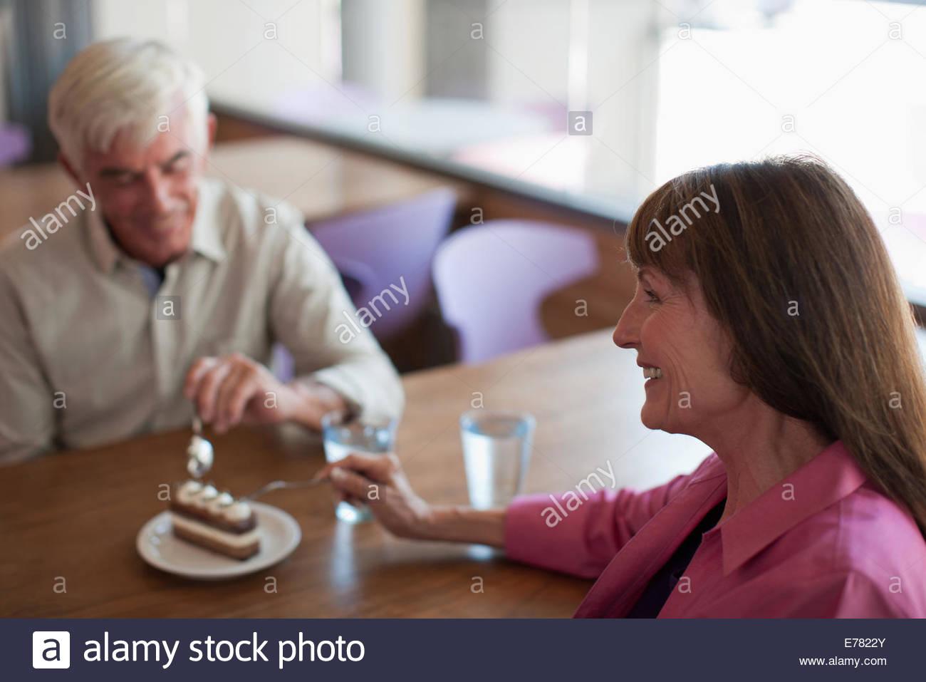 Older couple sharing dessert in cafe - Stock Image
