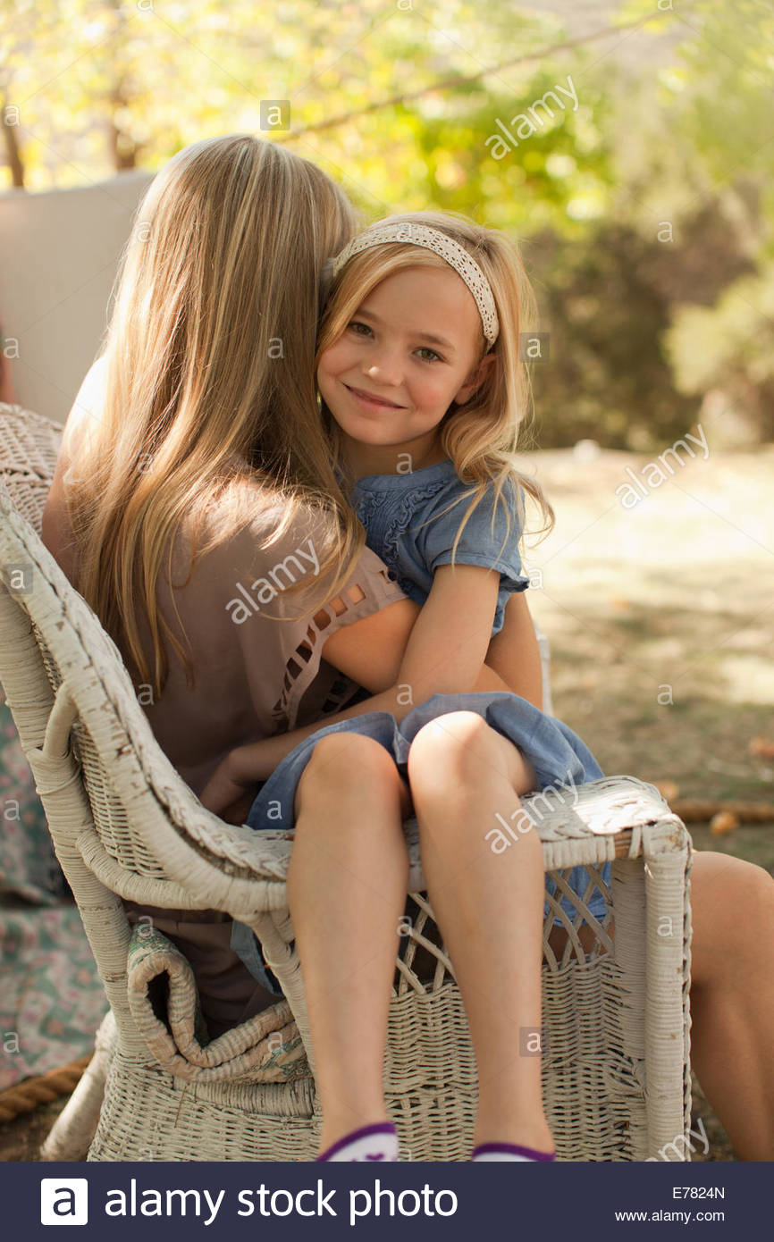 Mother hugging daughter outdoors Stock Photo