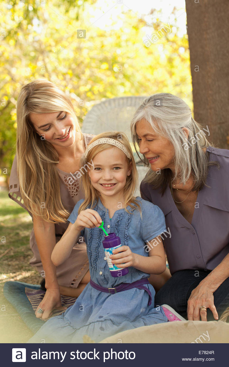 Three generations of women blowing bubbles - Stock Image