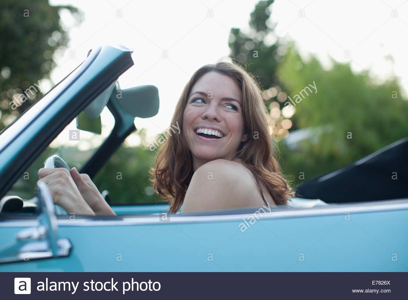 Smiling woman sitting in convertible - Stock Image