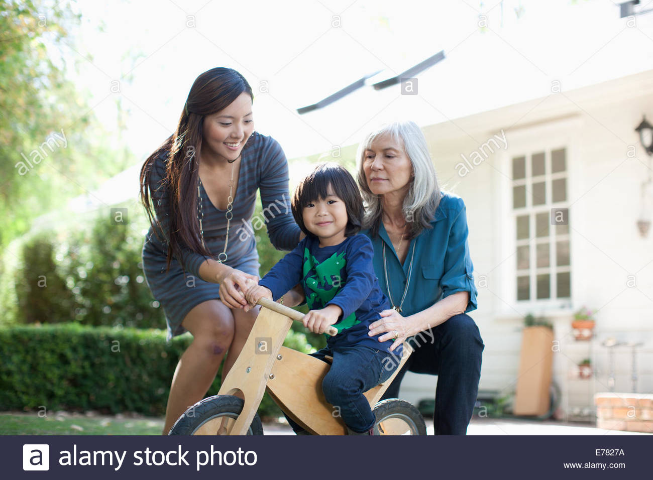 Mother and grandmother pushing boy on tricycle - Stock Image