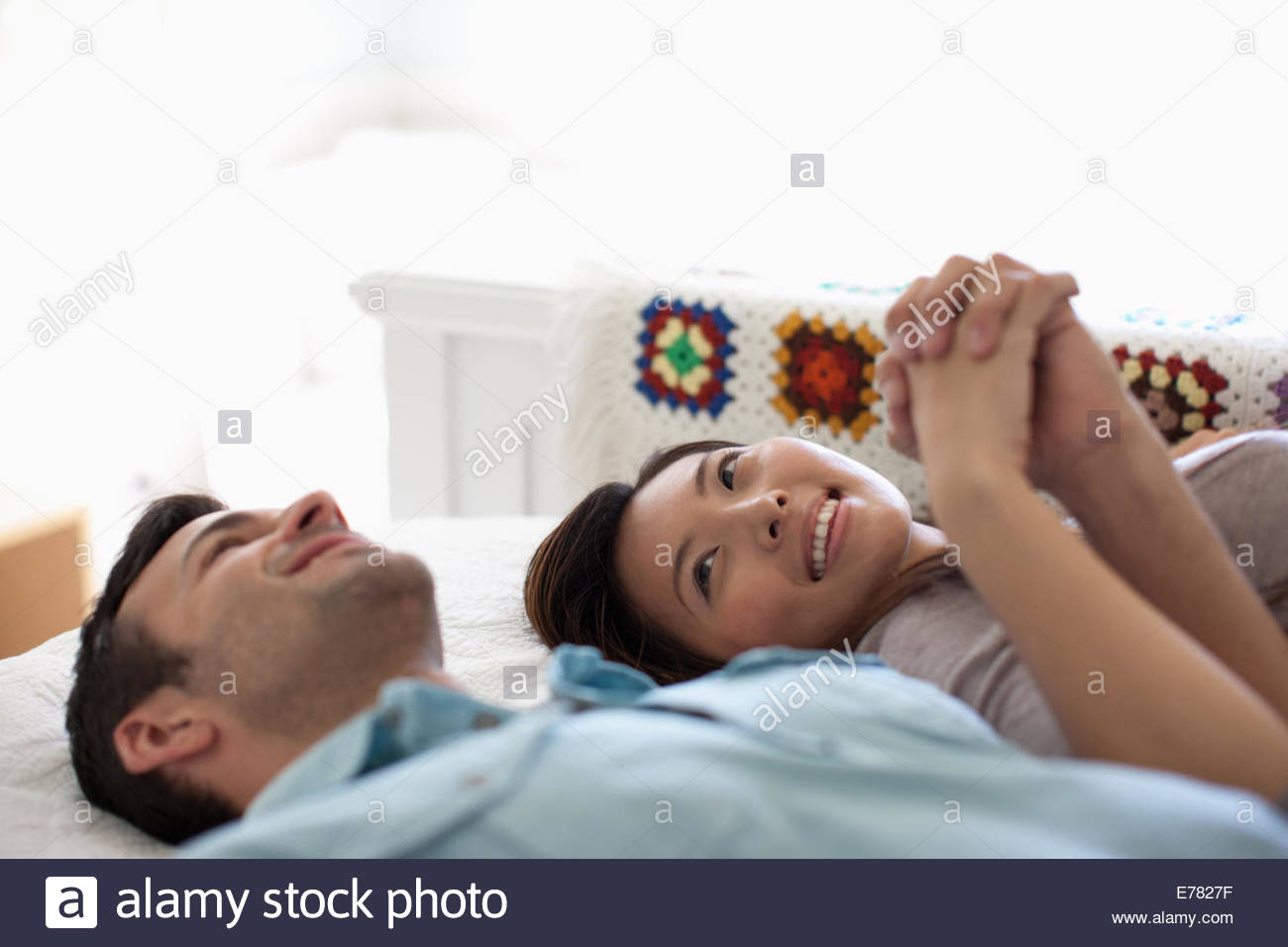Smiling couple holding hands on bed - Stock Image