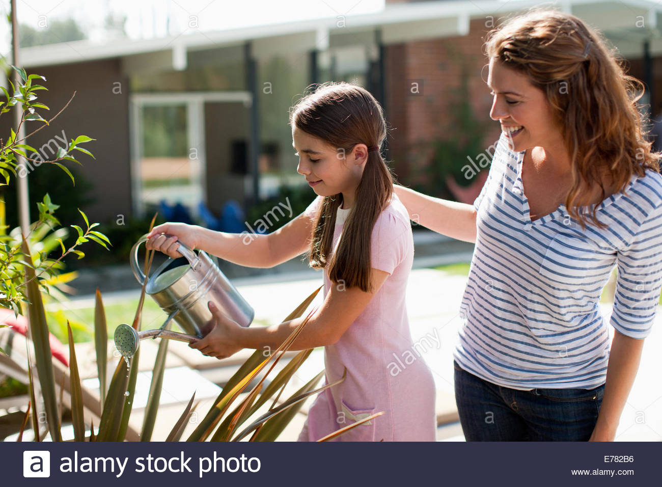 Mother and daughter watering plants outdoors - Stock Image