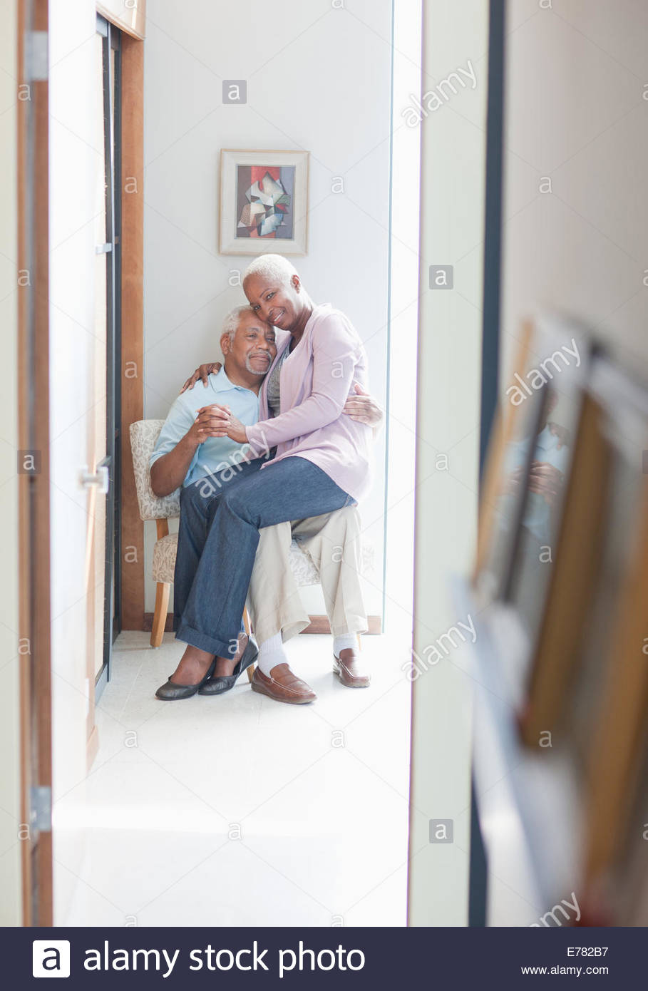 Older couple sitting together indoors - Stock Image