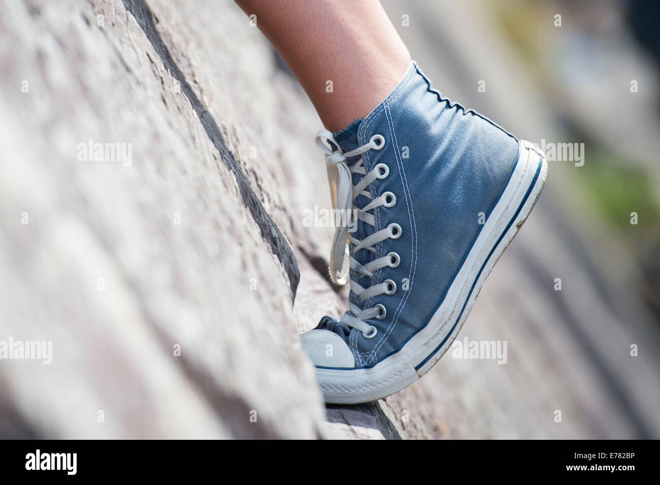 A girl's foot seen wearing Converse stretching while rock climbing. - Stock Image