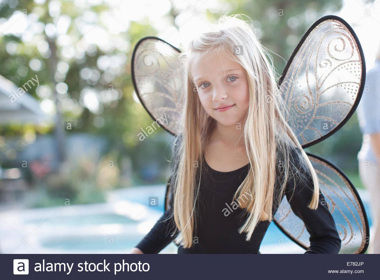 Girl wearing fairy wings in backyard - Stock Image