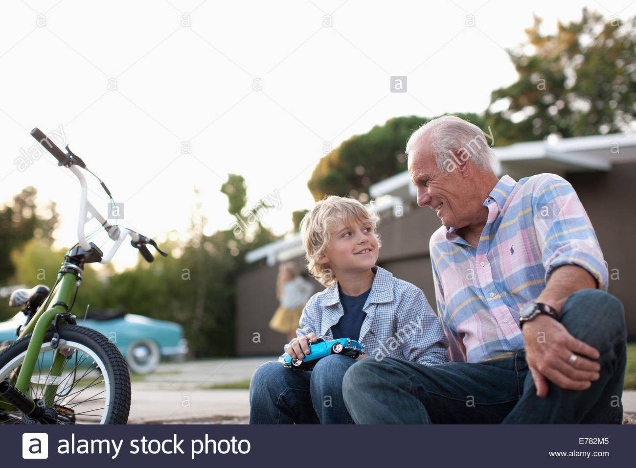Older man and grandson sitting together - Stock Image