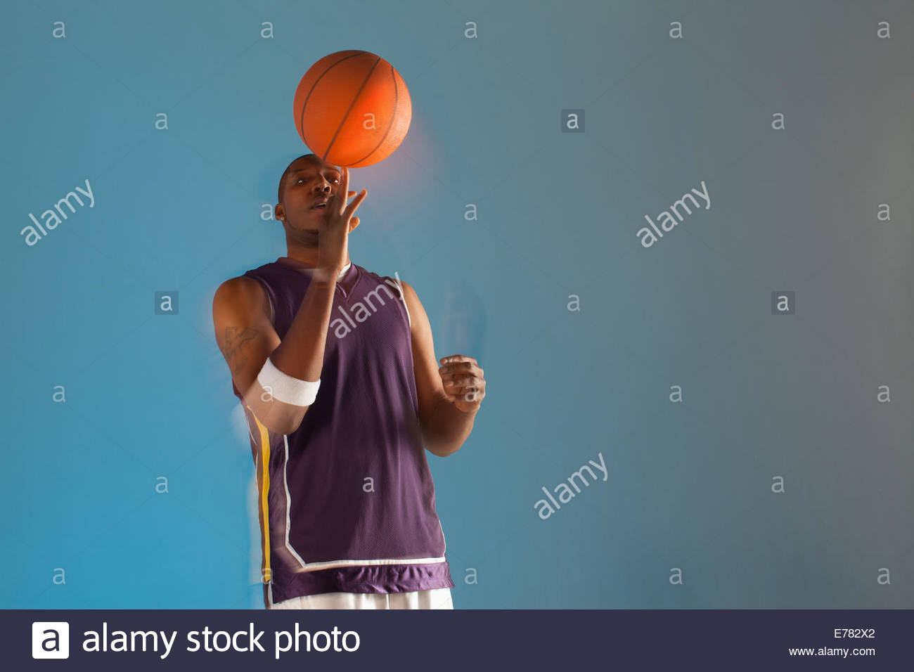 Basketball player balancing ball on one finger - Stock Image