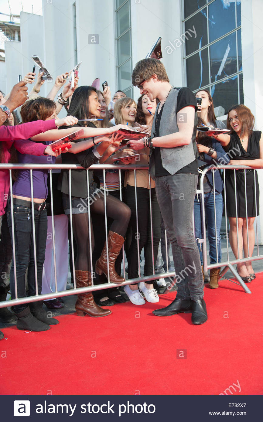 Celebrity signing autographs on red carpet - Stock Image