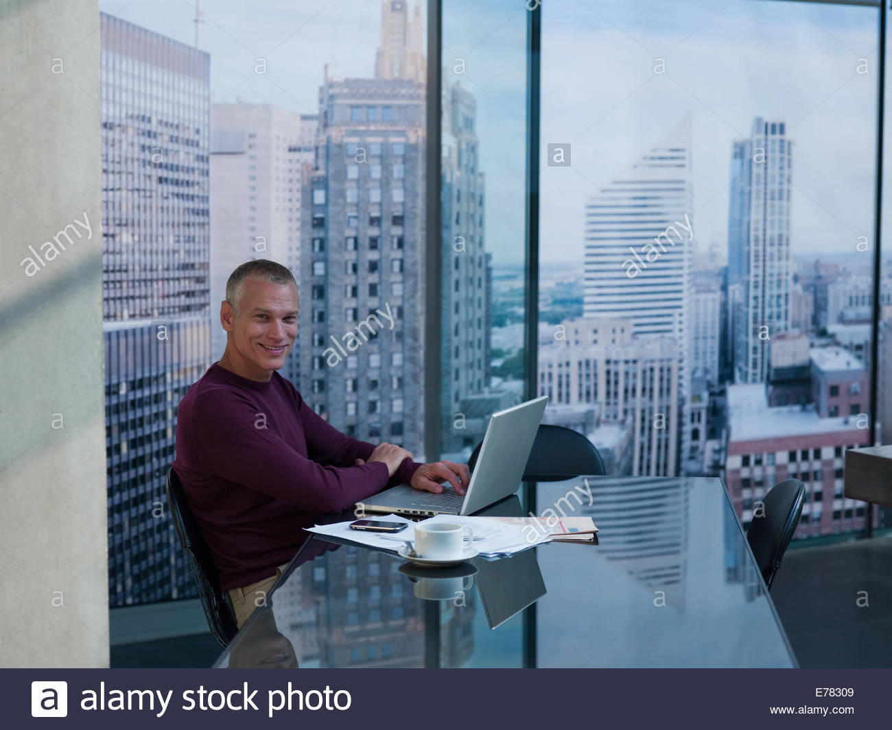 Businessman using laptop at desk - Stock Image