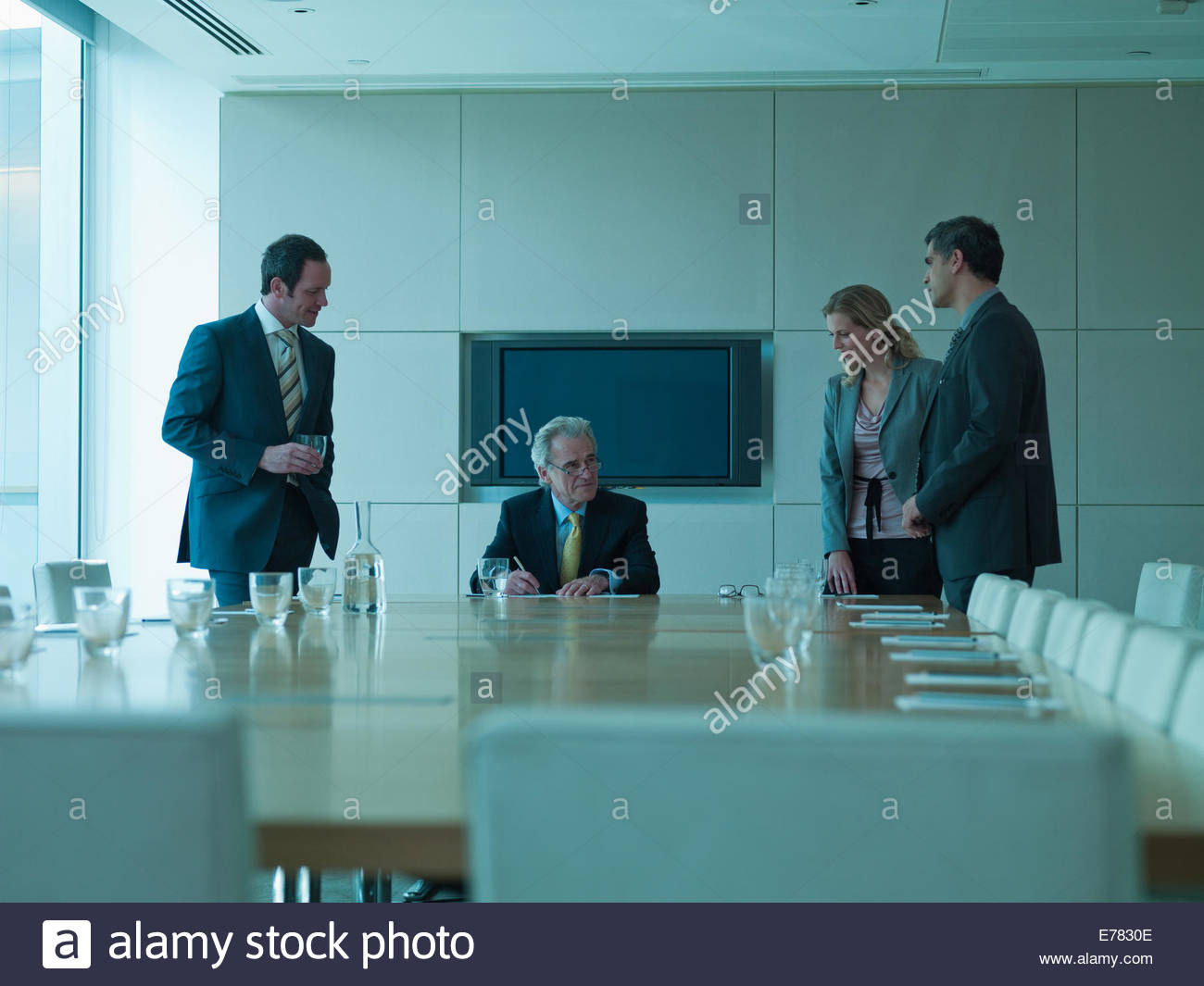 Business people watching boss sign contract - Stock Image