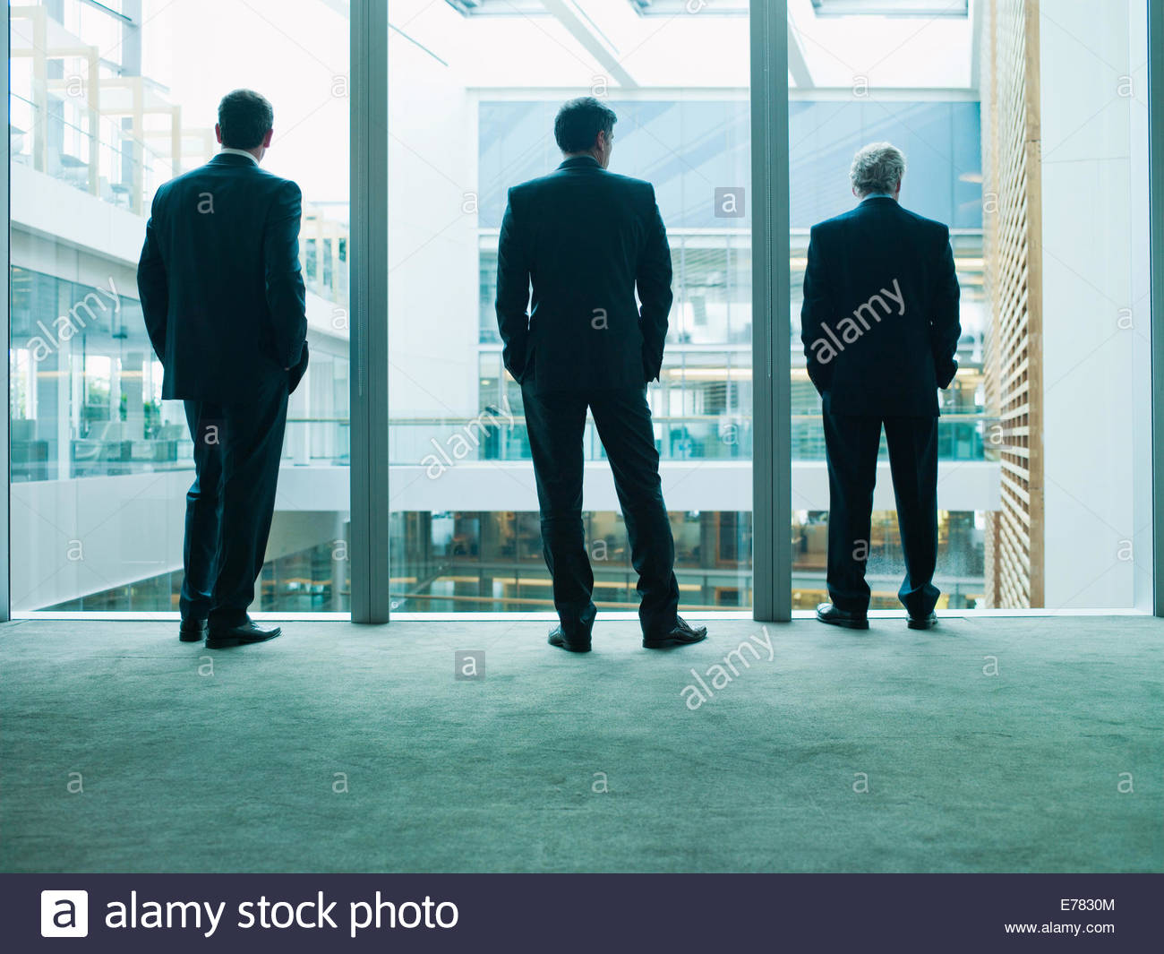 Business people looking out glass wall together - Stock Image