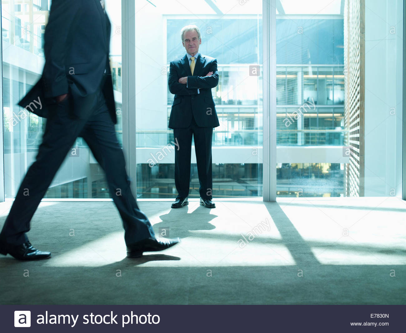 Businessman standing in corridor as co-worker rushes past - Stock Image