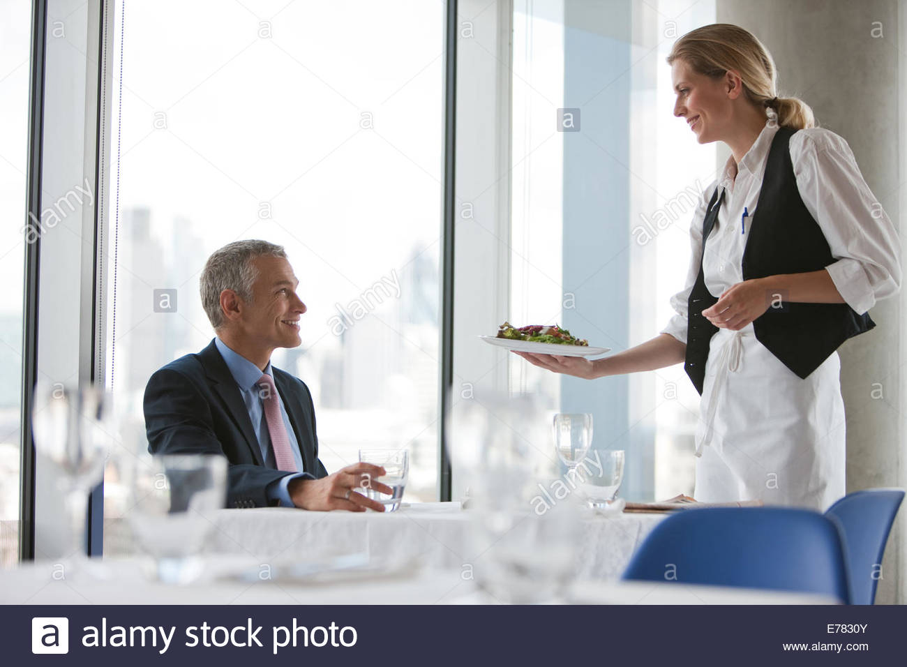 Waitress serving meal to businessman in restaurant - Stock Image