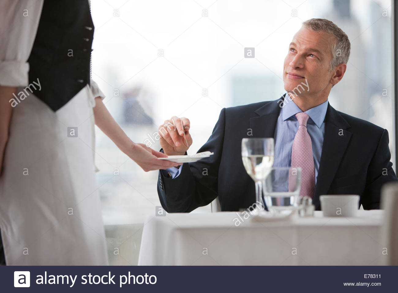 Businessman handing waitress credit card in restaurant - Stock Image