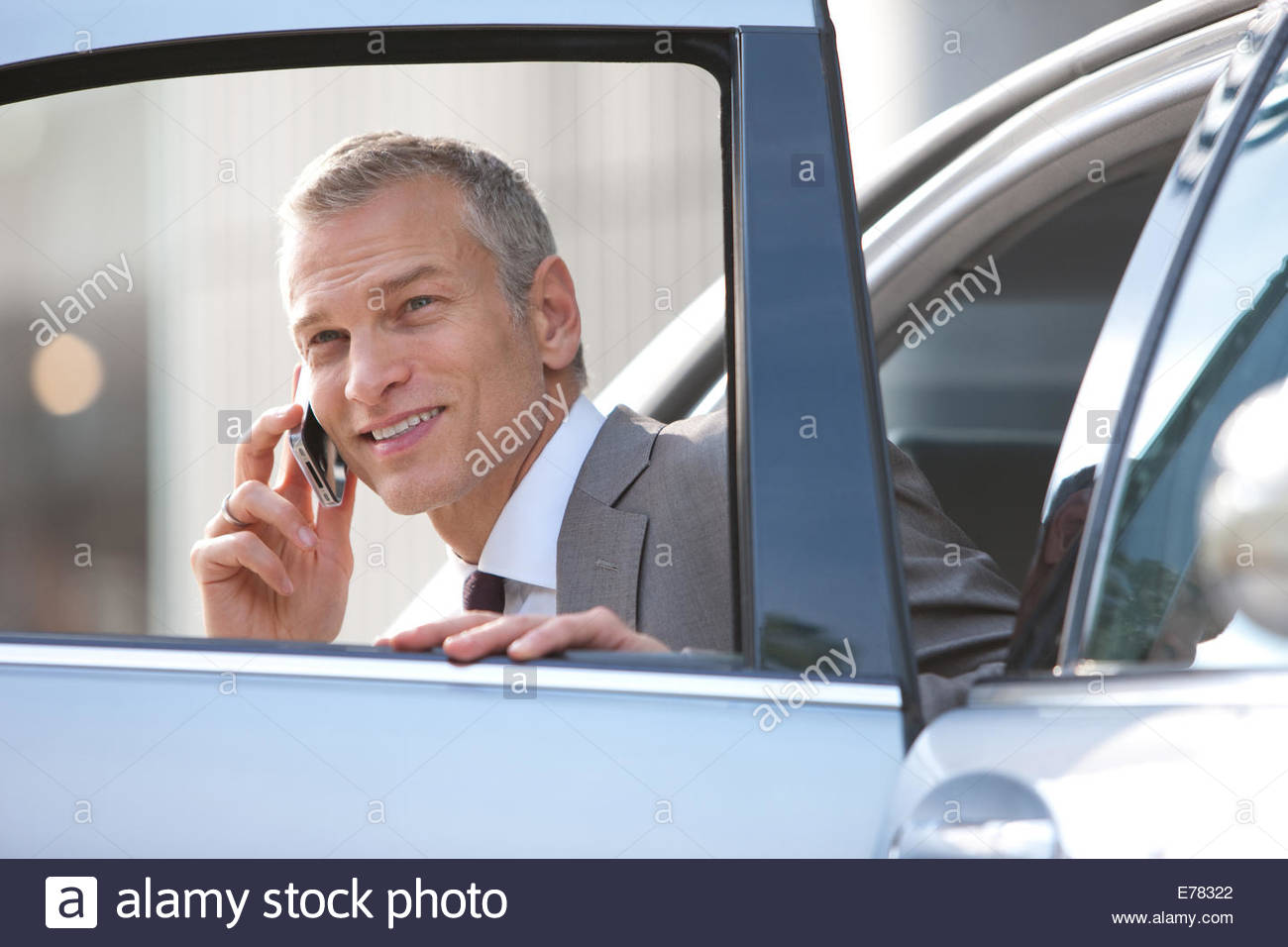 Businessman getting out of car talking with cell phone - Stock Image