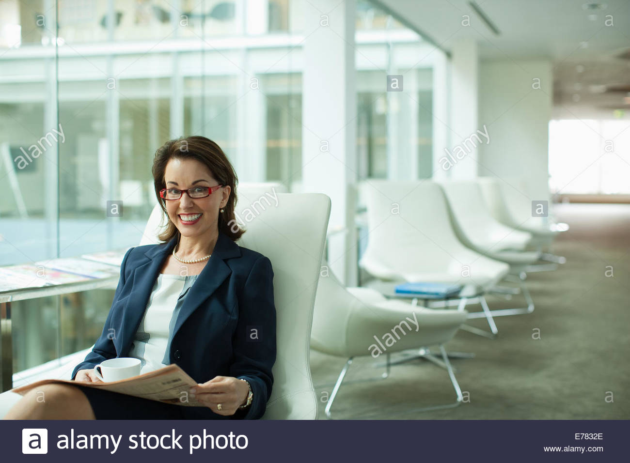 Businesswoman reading newspaper in waiting area - Stock Image
