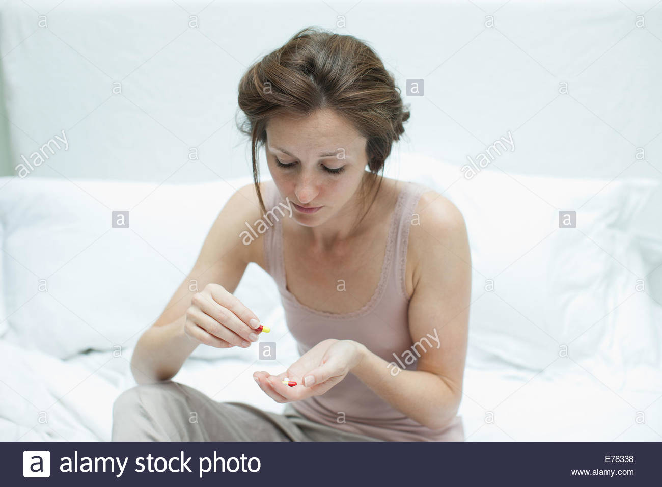 Woman holding pills and counting them - Stock Image