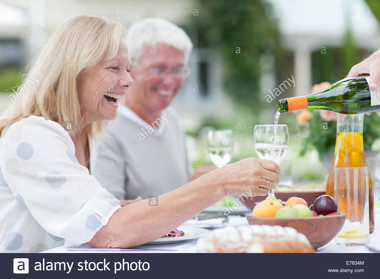 Senior adults enjoying wine at patio table - Stock Image