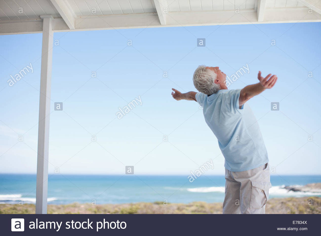 Senior man standing with arms outstretched - Stock Image