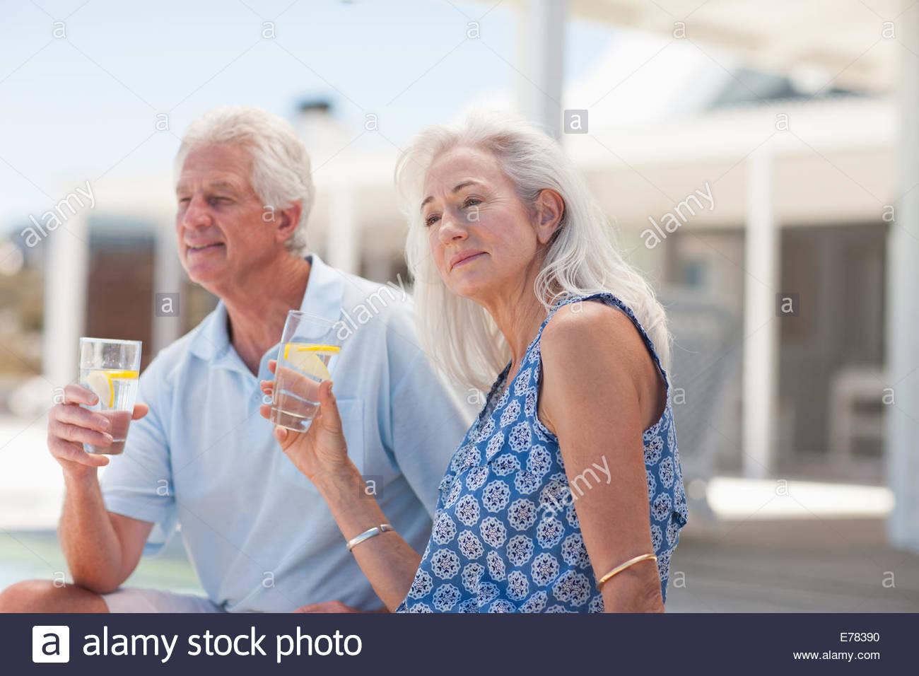 Senior couple drinking water on beach - Stock Image
