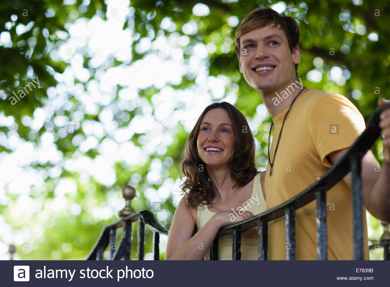 Smiling couple leaning on railing outdoors - Stock Image