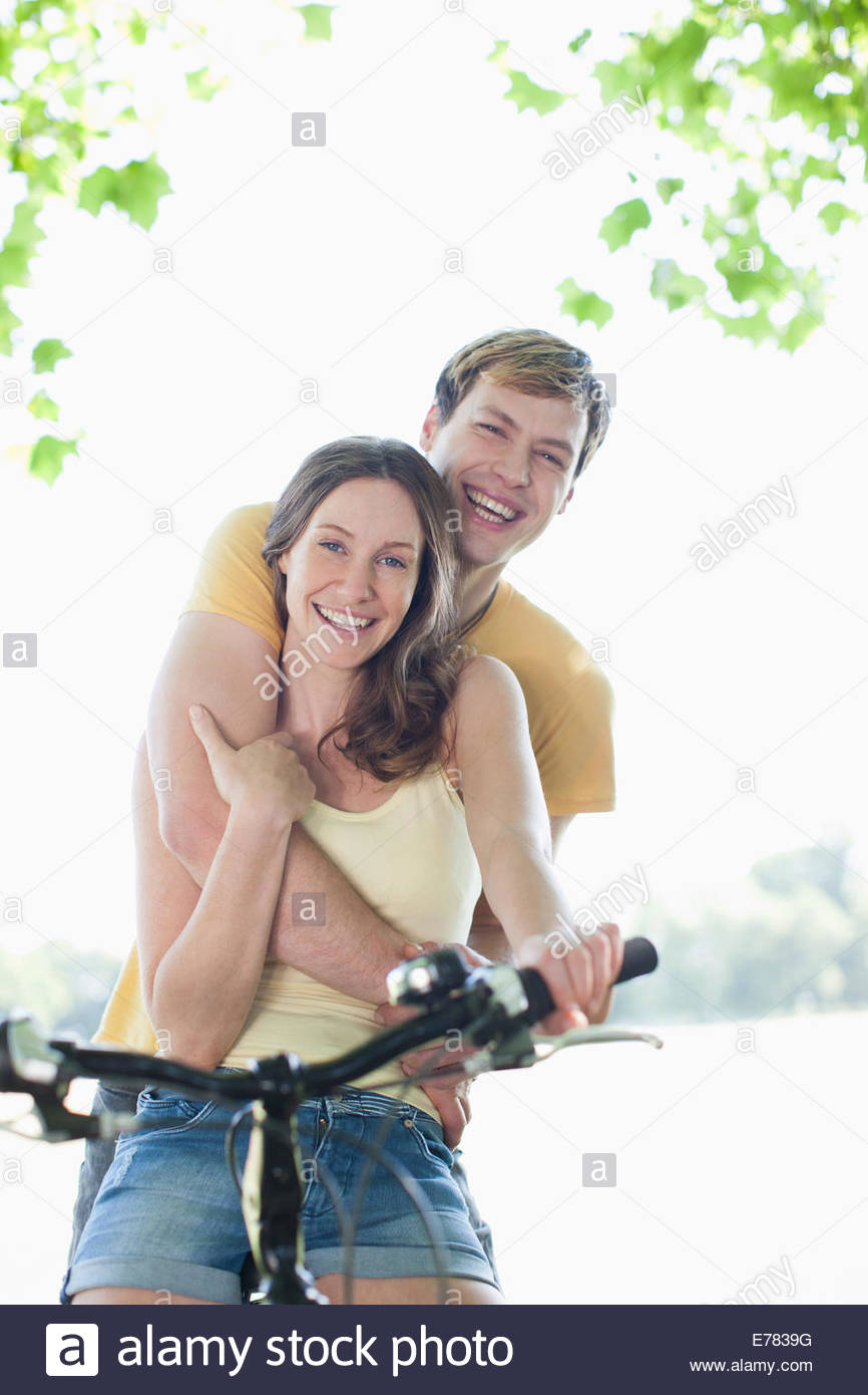 Smiling woman riding boyfriend on bicycle - Stock Image