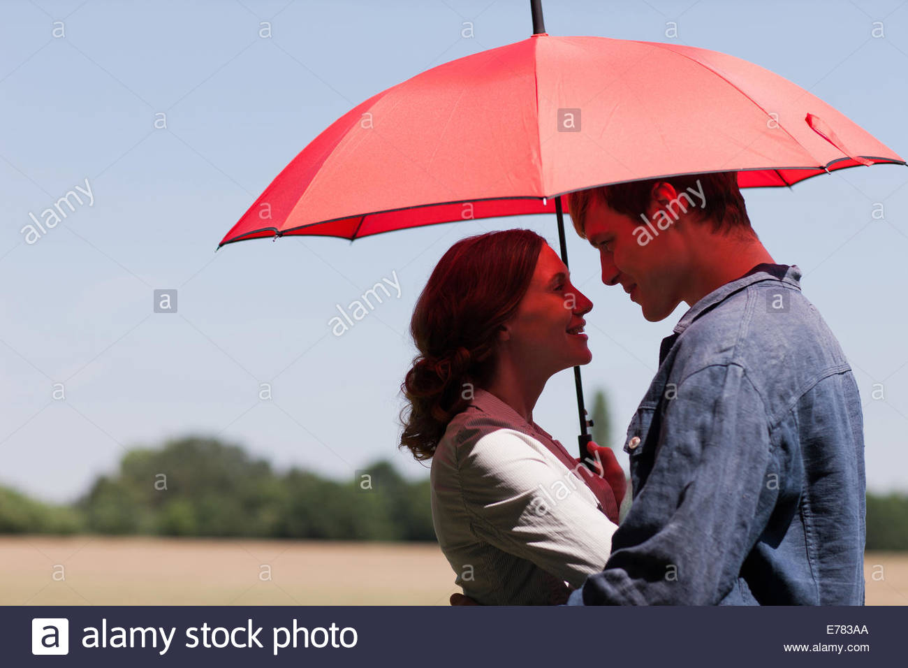 Couple hugging underneath red umbrella - Stock Image