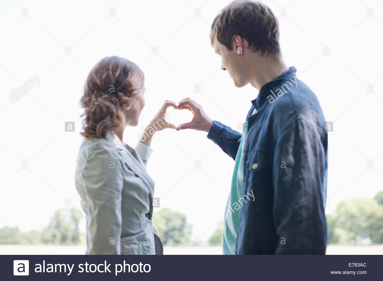 Smiling couple using hands to make heart shape - Stock Image