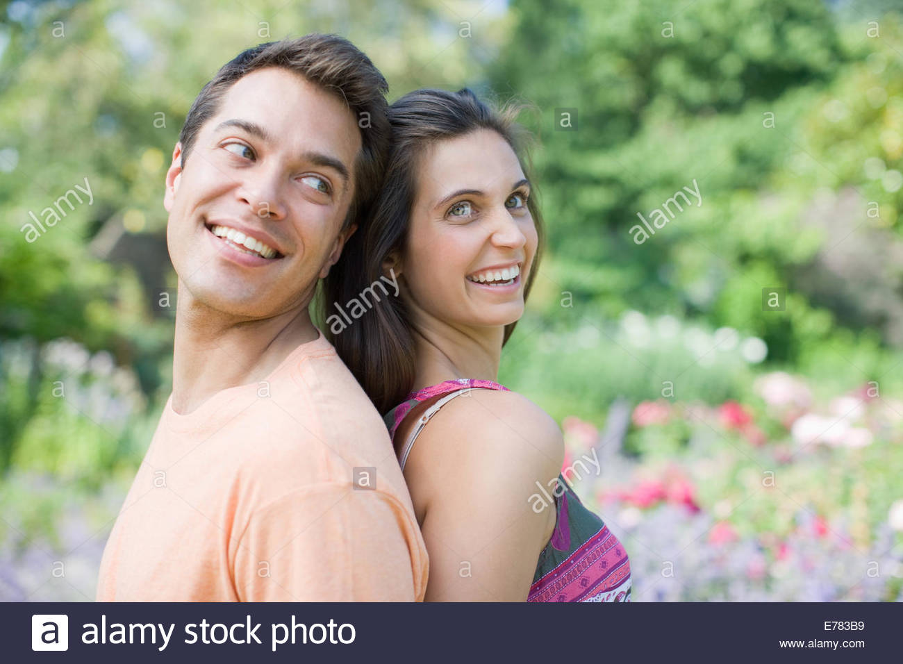 Smiling couple standing back to back in park - Stock Image