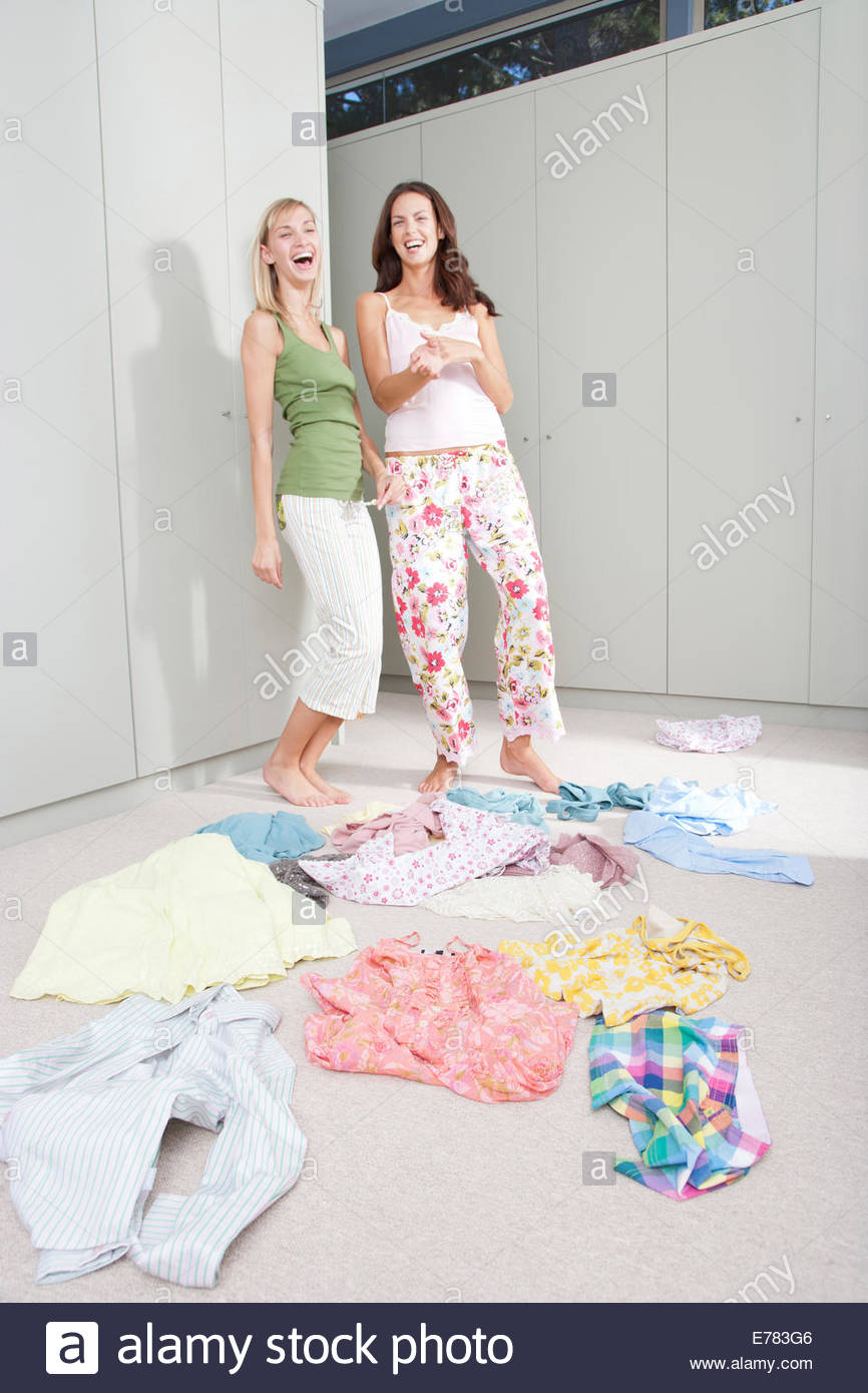 Two girlfriends in a bedroom going through a closet - Stock Image