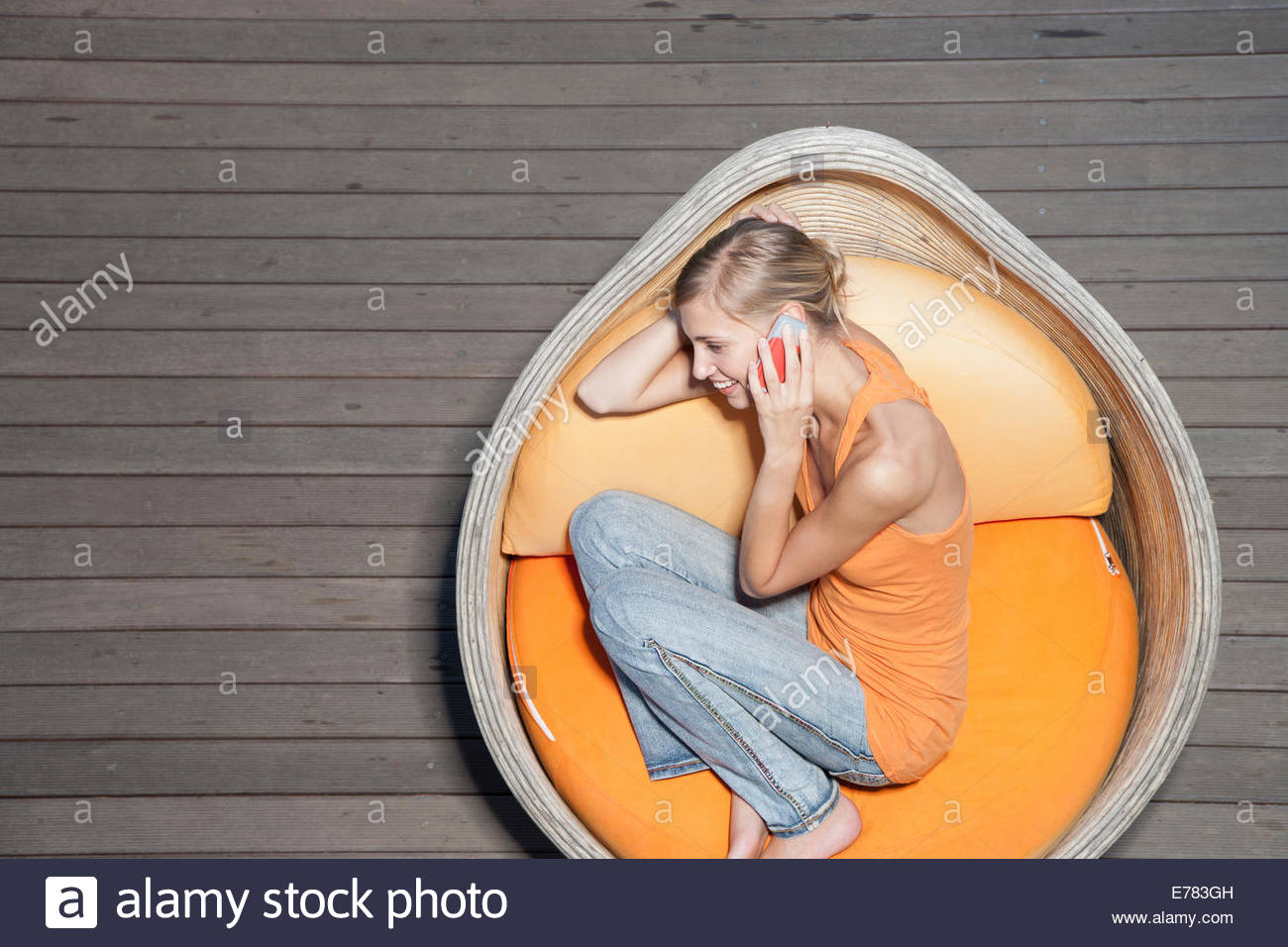 A young woman sitting on a deck on her cellular phone - Stock Image