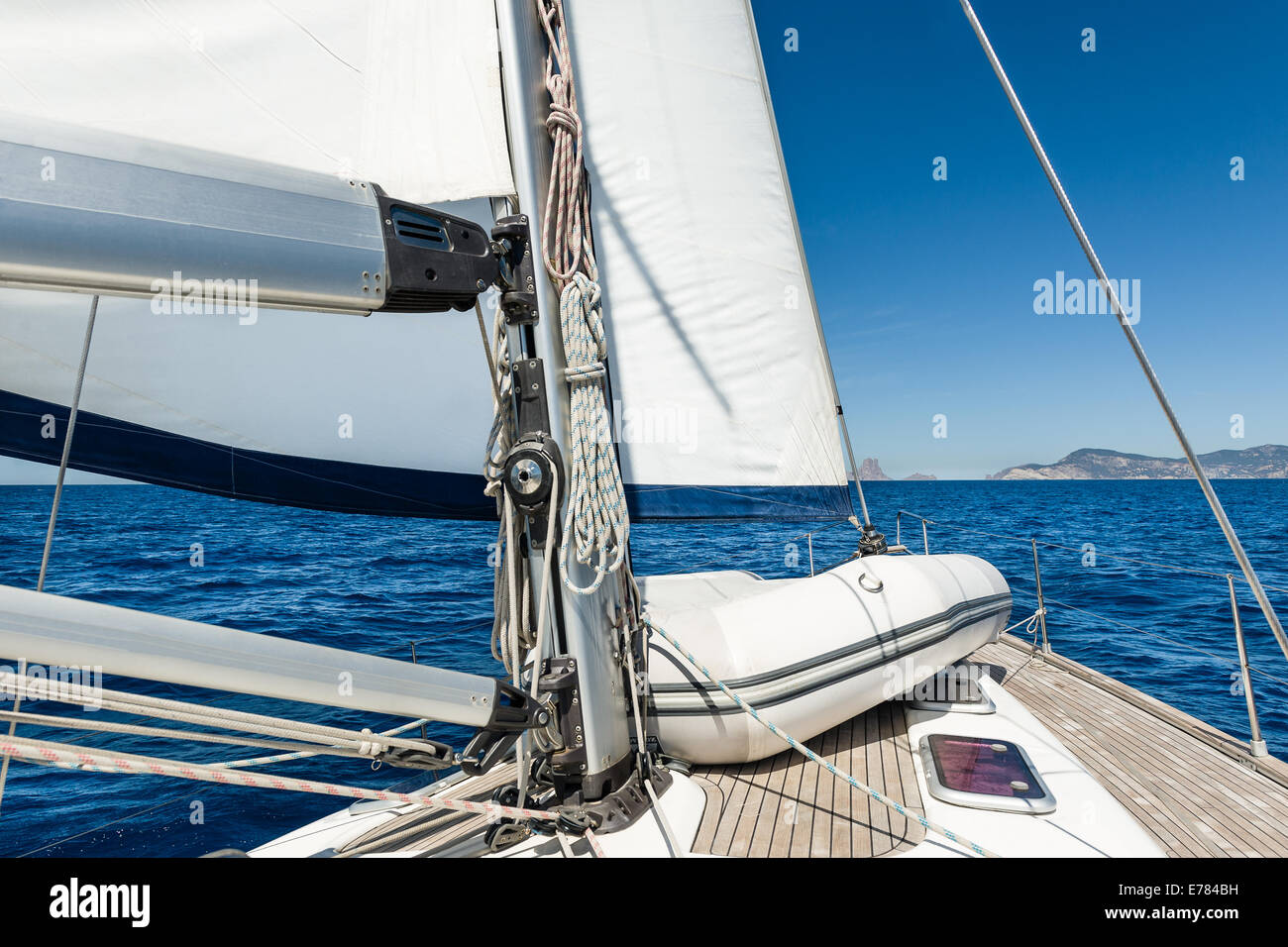 Sailing yacht going on her sails in calm weather - Stock Image