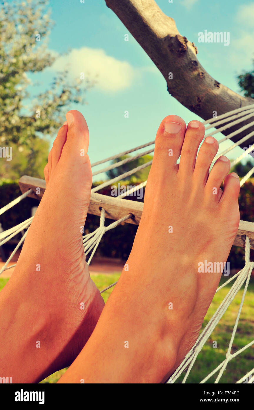 closeup of the bare feet of a man who is relaxing in a hammock - Stock Image