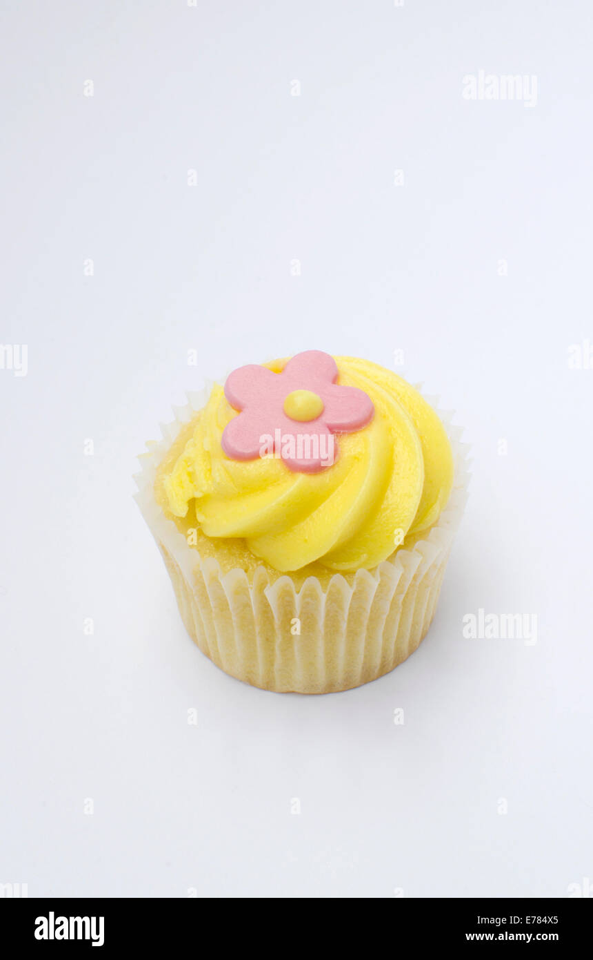 Mini Cupcake With Yellow Icing And Pink Flower Decoration On White