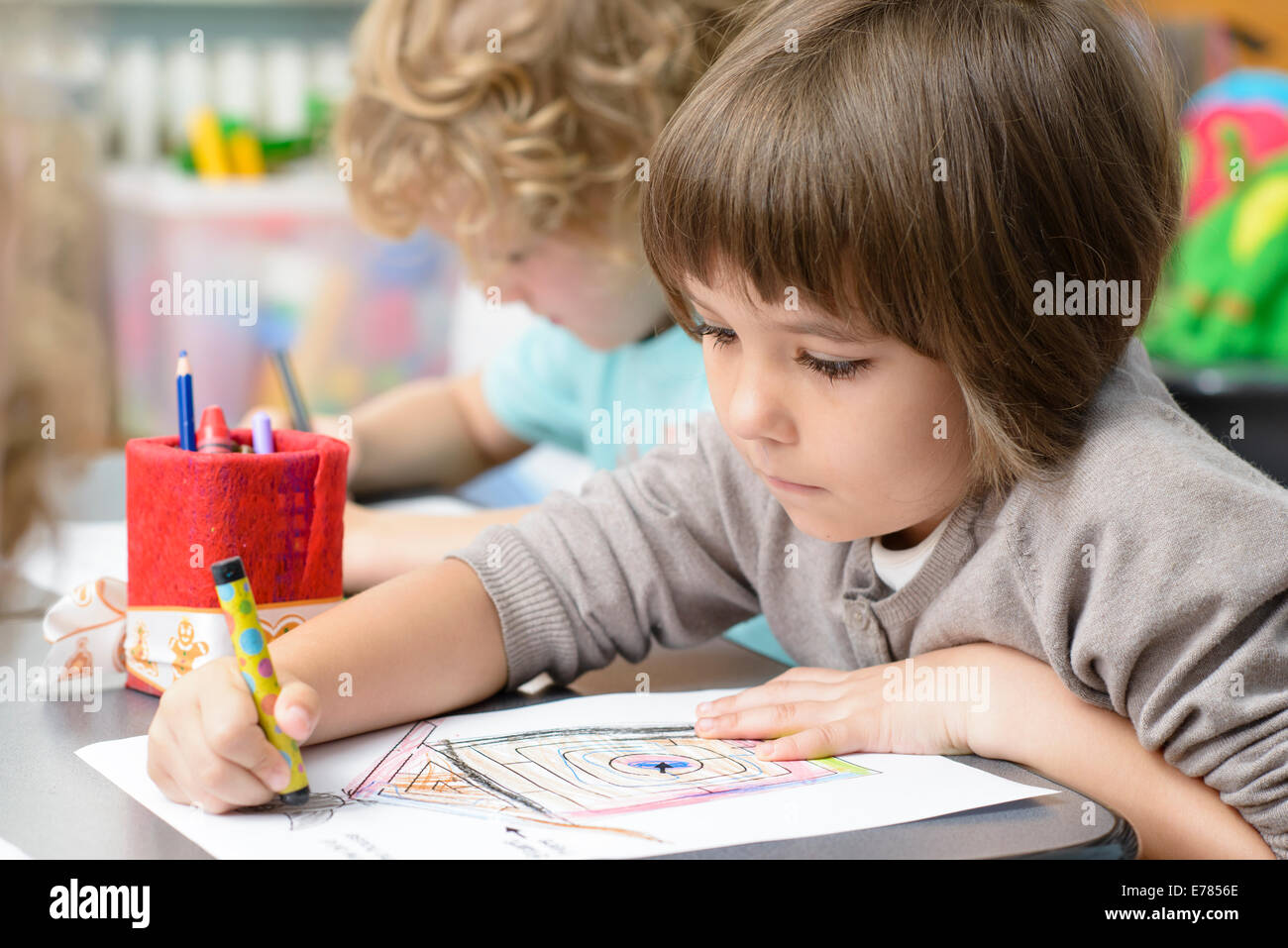 Two kids drawing at kindergarten - Stock Image
