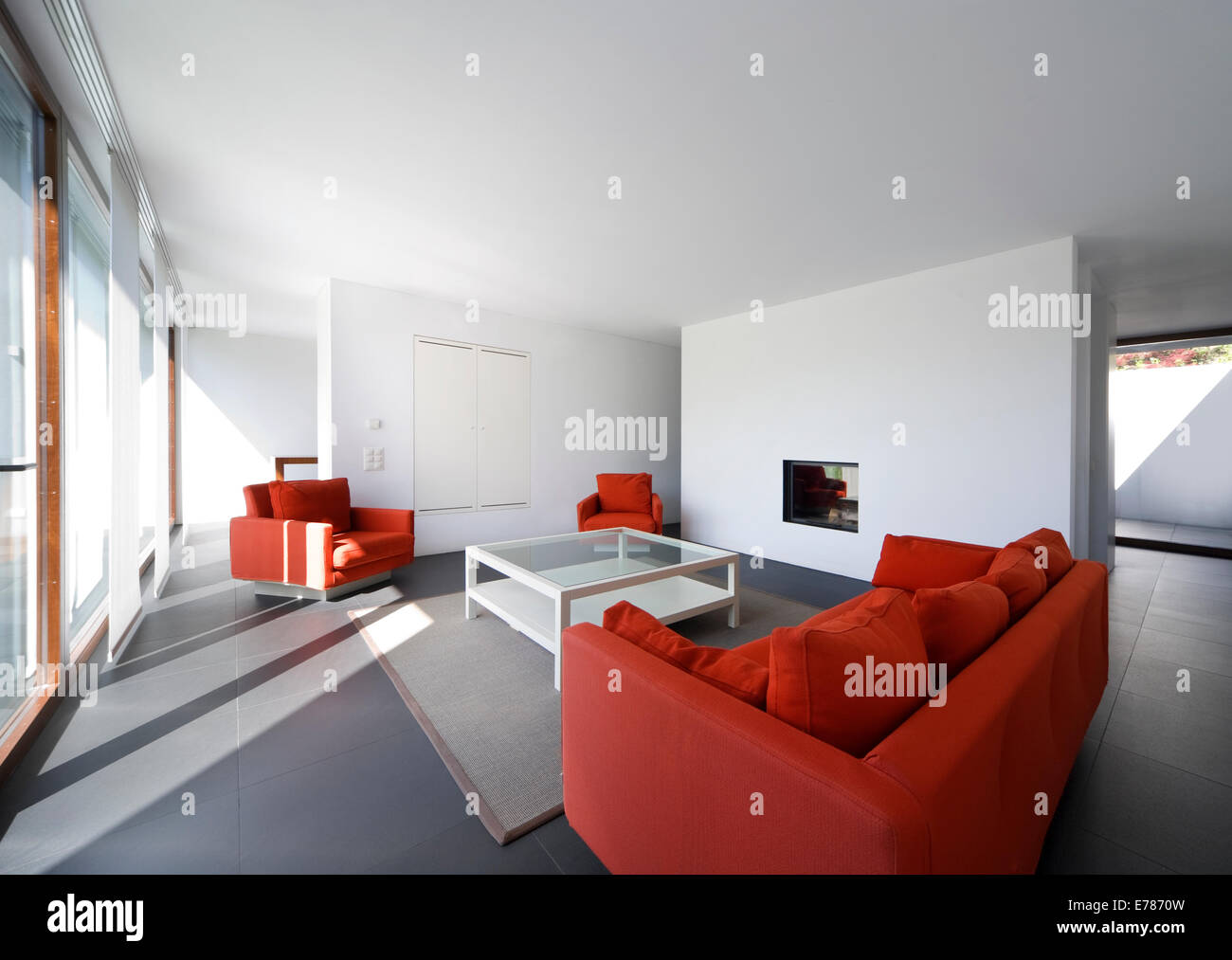 large living room with white walls and red couch Stock Photo