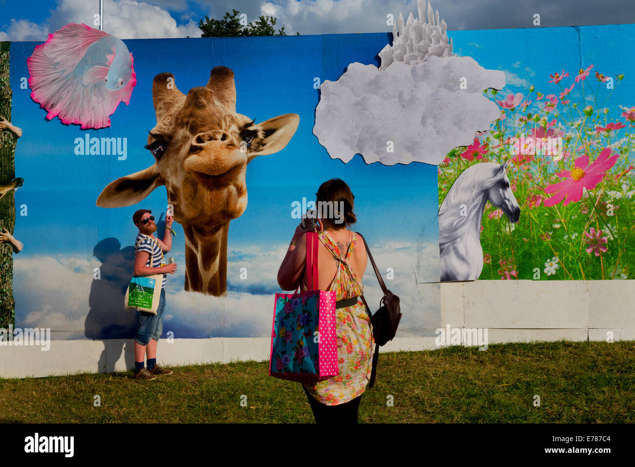 Glastonbury Festival 2014. Being photographed with a giraffe on the evolving graphic walls by Link Leisure - Stock Image
