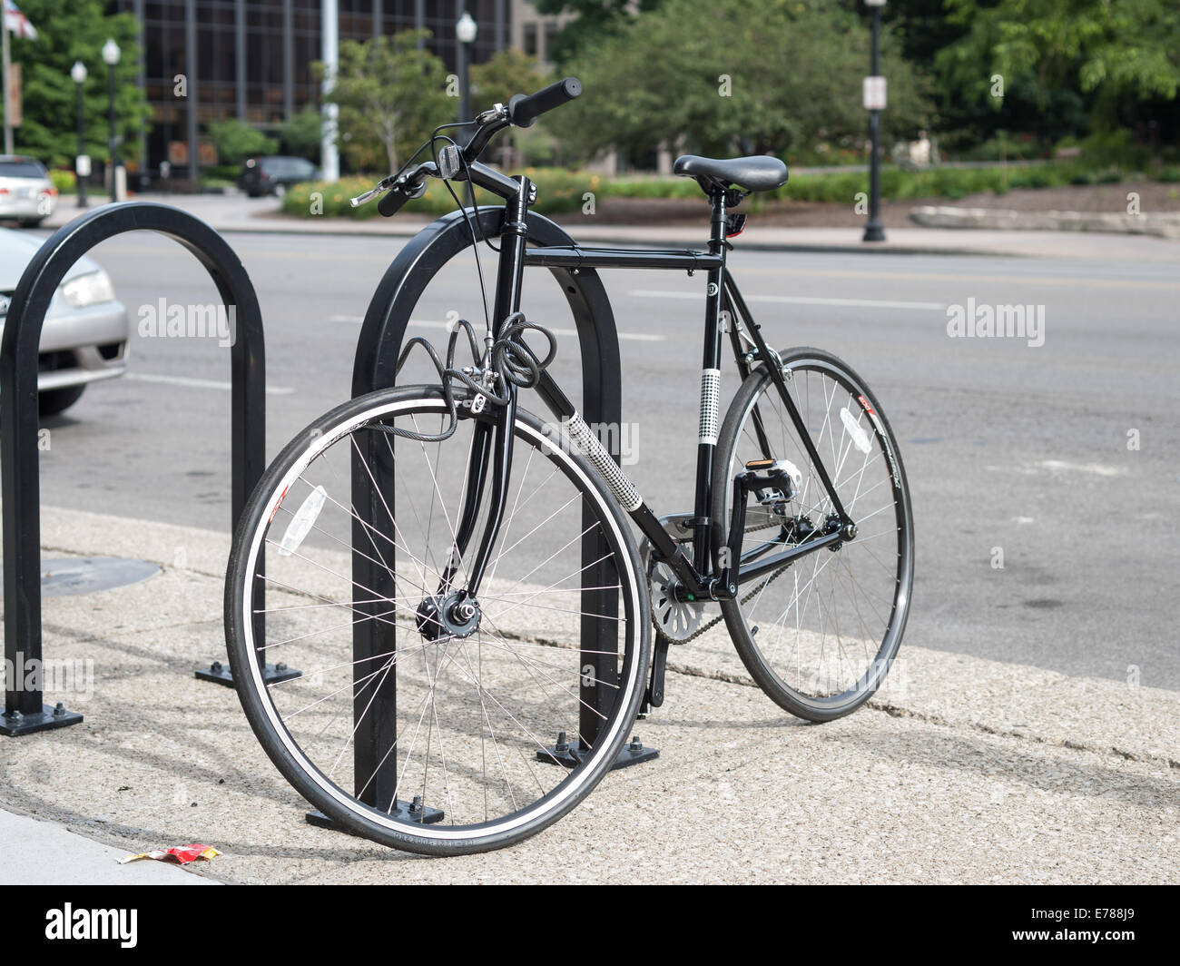 A bicycle parked at a bike rack next to the street in Columbus Ohio - Stock Image