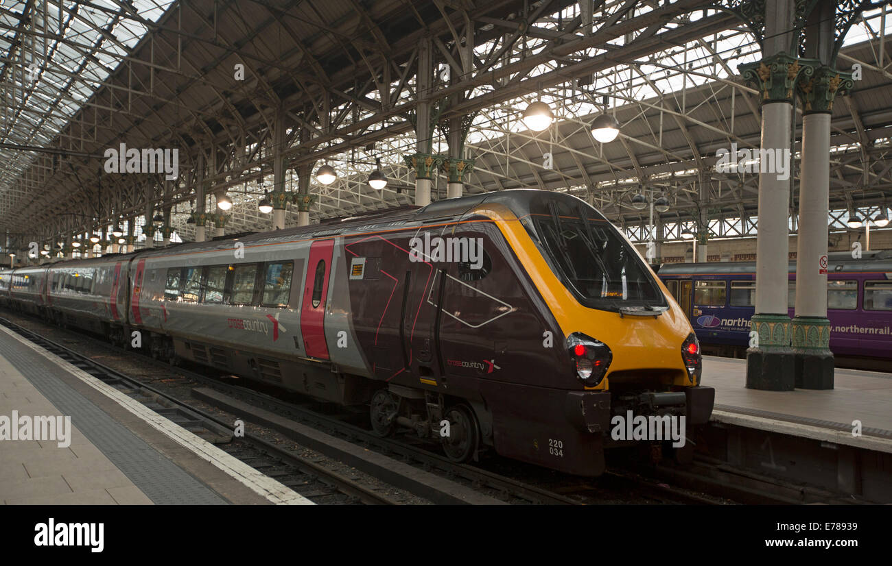 Train with modern diesel locomotive and passenger carriages at platform in Manchester railway station, England - Stock Image