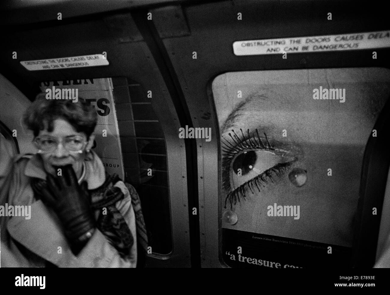 Woman in tube with Man Ray poster in the background. - Stock Image