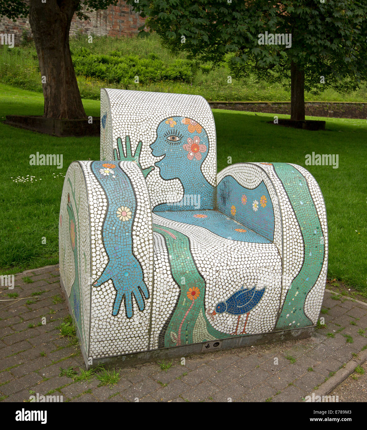 Street art, seating in public park, arm chair created with colourful mosaic tiles and smiling face design in Carlisle, Stock Photo