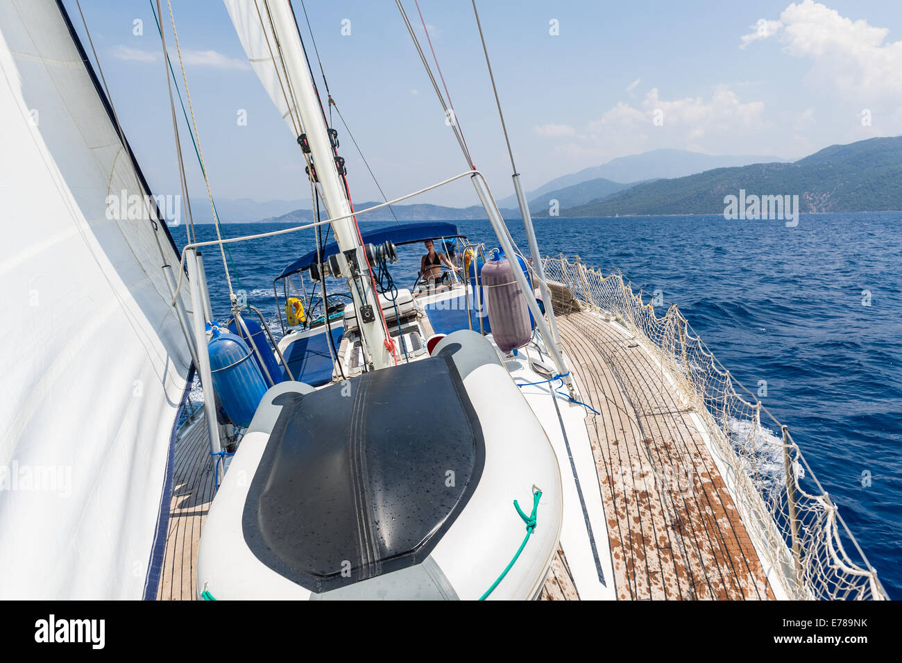 Sailing cruising yacht with women on the helm - Stock Image
