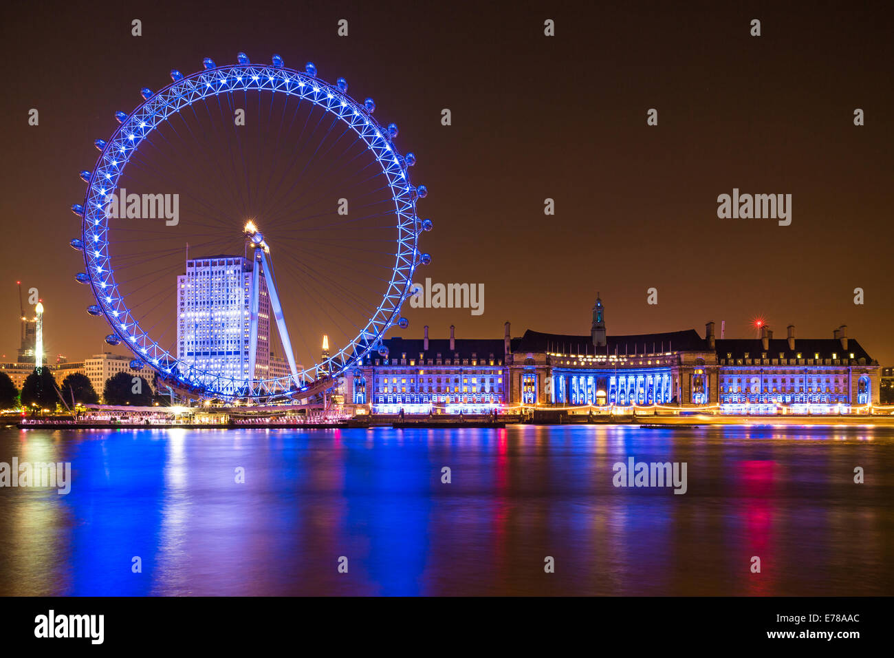 The London Eye, County Hall and Shell Centre buildings at night on the Thames river in London, England. - Stock Image