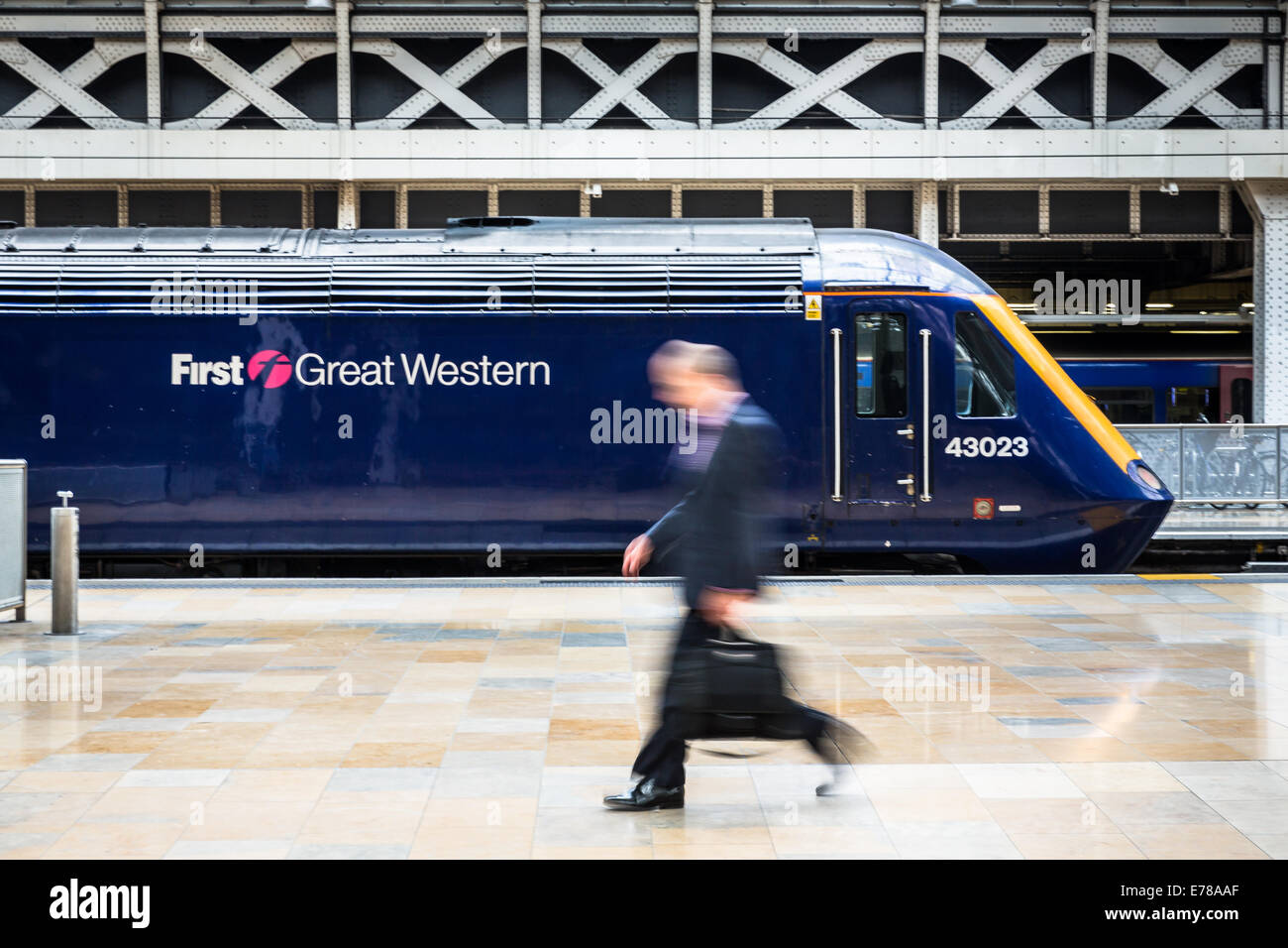 A business commuter walks passed a stationary First Great Western Intercity train at Paddington Station in London, - Stock Image