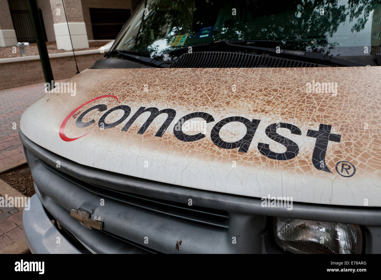 Dirty, worn-out, fading Comcast logo on service van - Arlington, Virginia USA - Stock Image
