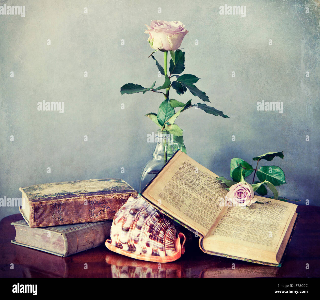 Interior still life, composition of antique books, pink roses and shell with retro desaturated Instagram-like effects Stock Photo
